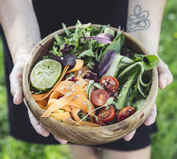 přírodní mísa z teakového dřeva na salát s pestrým zeleninovým salátem v dlaních
