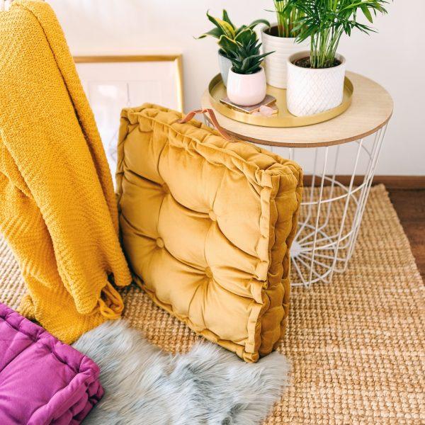 Měkký nadýchaný čtvercový polštář hořčičné barvy jako doplněk do boho interiéru